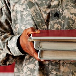 servicemember holding school books
