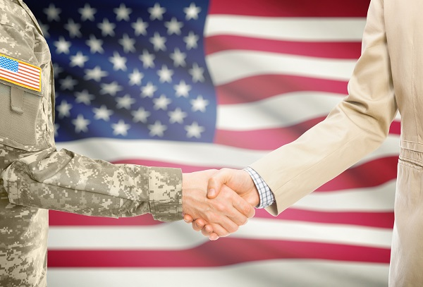 two men shaking hands, one of them is in a suit, the other is in military uniform