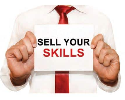 "Man holding a sign that says ""Sell Your Skills"""