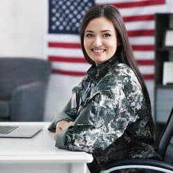army woman sitting at desk in a wheelchair smiling in to camera