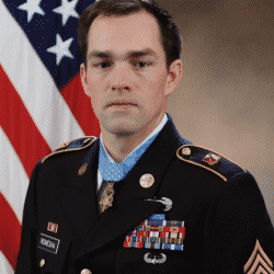 Clint Romesha poses for camera in full military dress uniform with US Flag in the background