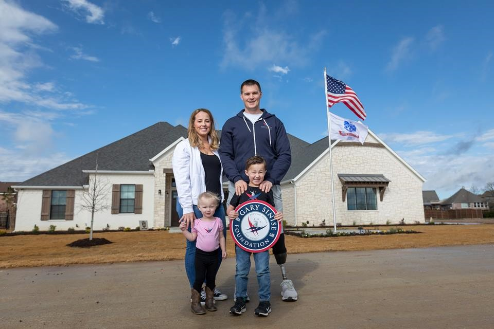 Disabled Veteran with his family standing outside their smart home