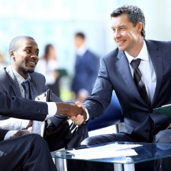 business people shaking hands with one another in a company setting