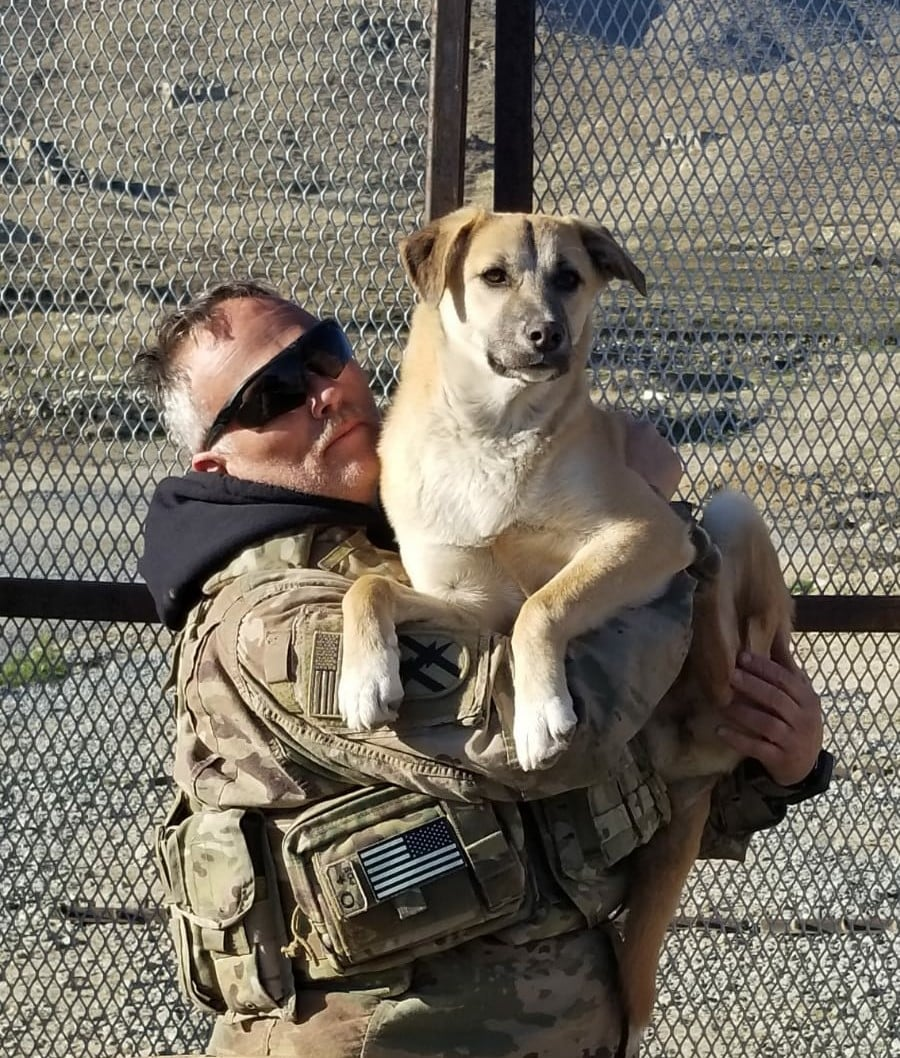 U.S. Soldier standing in uniform holding his shelter dog in his arms