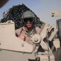Spencer Velez poses in uniform) in a military vehicle