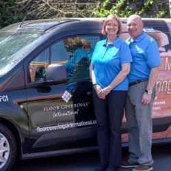 Lorrie, Lewis Willey stand posing in front of their Floor Coverings van in Colorado Springs, CO