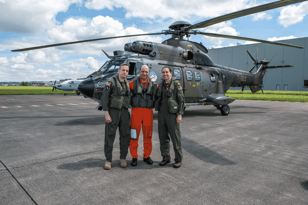 Three uniformed U.S. soldiers standing outside Army helicopter