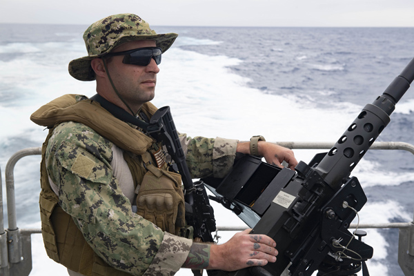 Gunner's Mate Brandon Sturhann sits aboard the USNS Carson City in the Atlantic Ocean maning awatch with machine gun