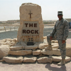 Soldire stands in uniform next to rock called The Rock