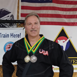 The Grandmaster stands with medals around his neck and the American Flag in the backgrounf