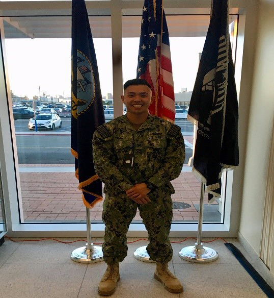 Anthony Tran standing in uniform with flags in the background