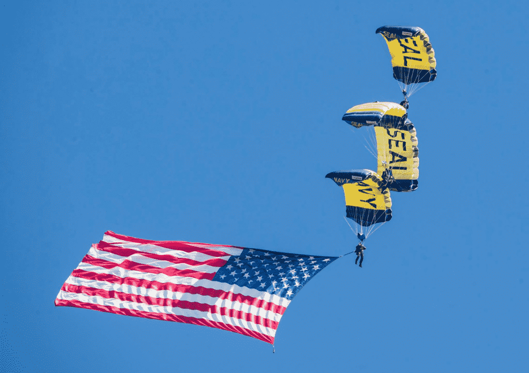 Skydivers in the air with an American Flag attached