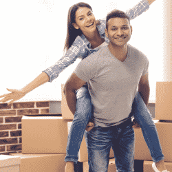 Man and woman pictured with moving boxes in background