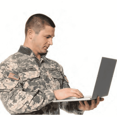 Soldier dressed in fatiques looking at his laptop