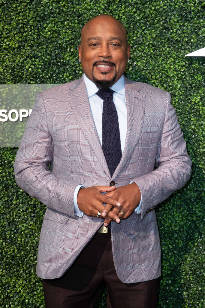 Daymond John standing wearing a gray suit