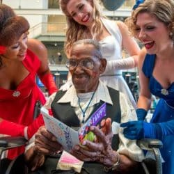 Oldest World War ll veteran sitting in wheelchair receives birthday card from womens' singing group