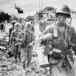Soldiers pictured in uniform walking through field with helicopter flying low in the background during Vietnam War