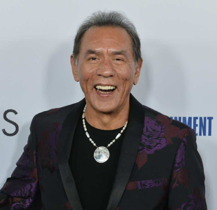 Wes Studi pictured smiling, wearing a dark suit and silver necklace, at event premiere