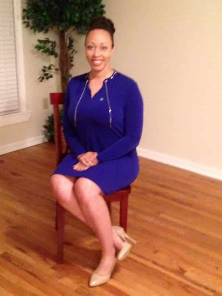 Keione A. Gordon sitting in a chair wearing a dark blue dressin a professional photo