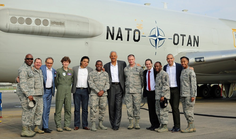 Stedman Graham poses with several servicemembers outside in front of a large military plane