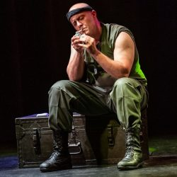 Douglas Taurel is sitting onstage in a green shirt, pants and headband lighting a cigarette
