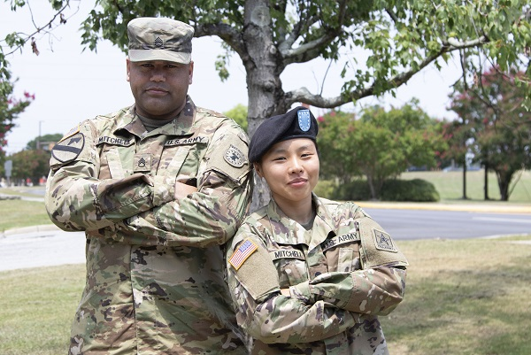 U.S. Military wife and husband in uniform standing side by side with arms folded