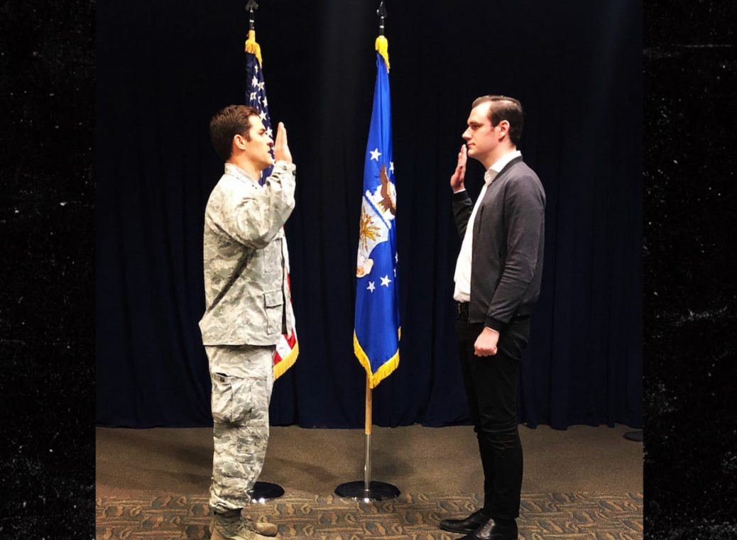 Cooper Hefner in fatigues taking the oath with flag in background