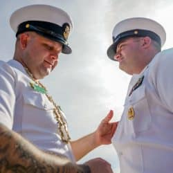 Master Chief Sonar Technician (Submarine) Michael Wangen II pins his replacement abaord Navy ship