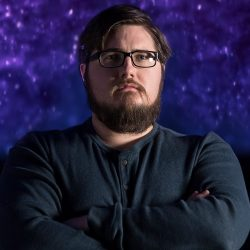 Joshua Carrol pictured with an dark purple and black background wearing a dark sweater with arms folded