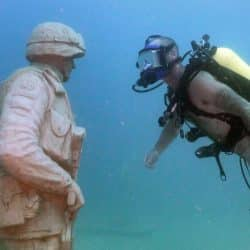 Scuba diver sees statue of himself at a underwater memorial