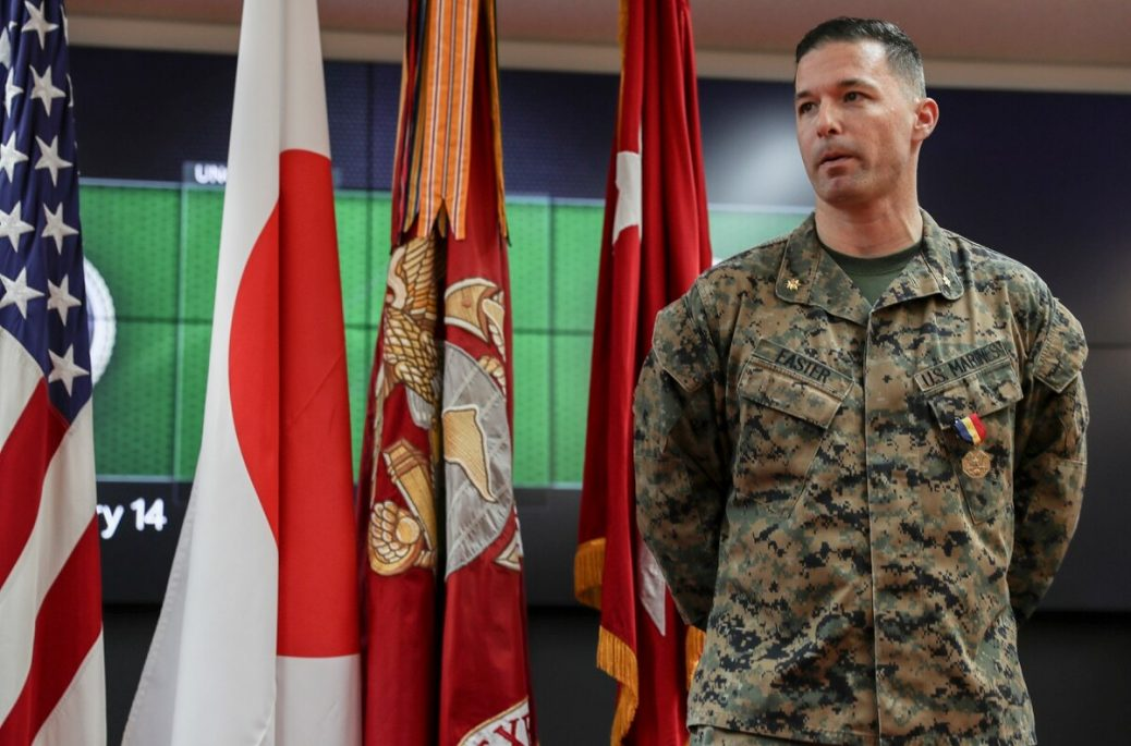 Marine Maj. William Easter stands in front of the color guard flags at his award ceremony