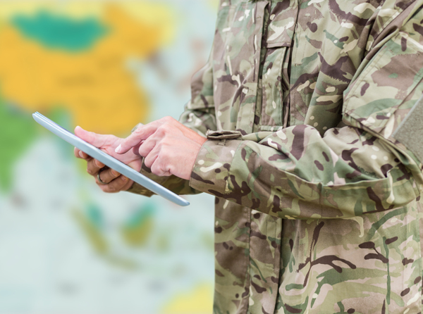 Soldier with tablet standing in front of a blurry map