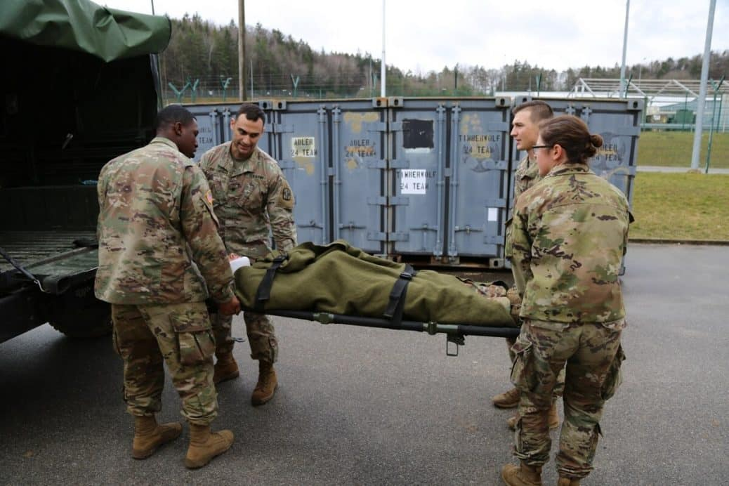 Army medical personnel load stretcher into a military vehicle