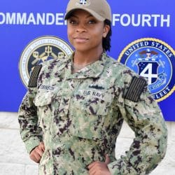Information Systems Technician Petty Officer 2nd Class (SW) Laurin Robinson stands with hands on hips confidently in her uniform