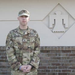 Confident young U.S. Soldier in uniform stands outside of a building