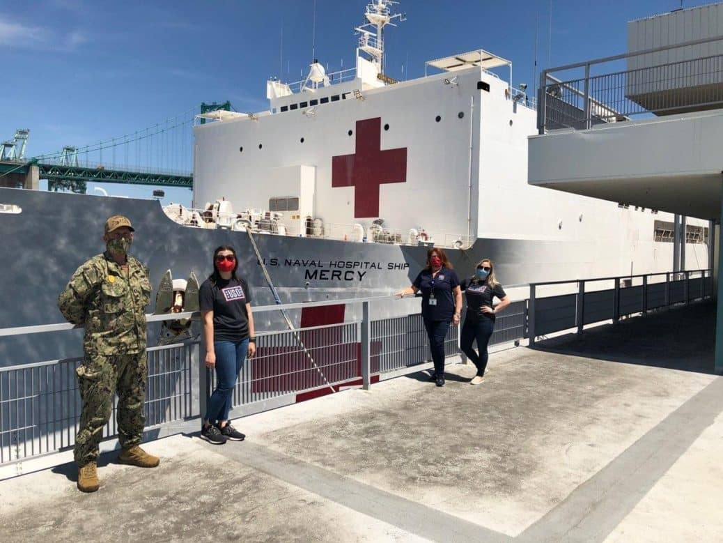 USO members and servicemembers stand on the dock in front of Red Cross Ship