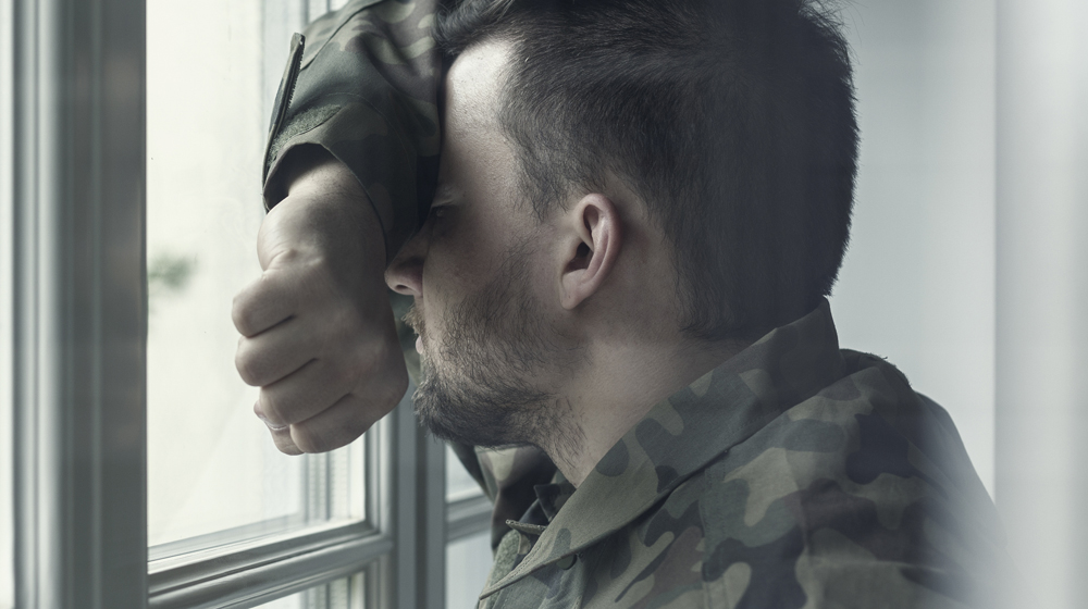 Depressed soldier leaning against the window covering his face with his arm